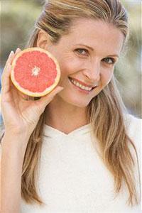 Женщина держит грейпфрукт