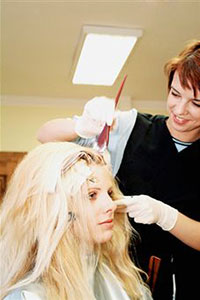 Девушка красит волосы в салоне